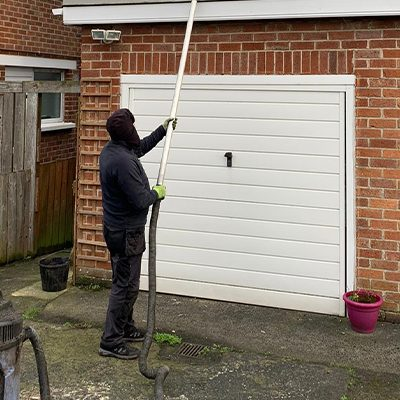 An image of a man using a gutter cleaning vacuum cleaner